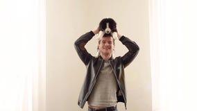 Счастливый человек ослабляя дома с шаловливым щенком на его плечах усмехаться и смеяться акции видеоматериалы