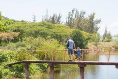 Счастливый человек отца при его маленькая дочь идя через деревянный мост моря Стоковая Фотография