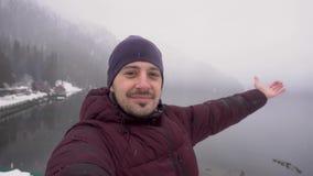 Счастливый человек путешественника принимая selfie и показывая озеро Ritsa в абхазии День Snowy в зиме сток-видео