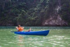 Счастливый человек сидя в шлюпке каяка на озере ослабляя стоковые фотографии rf