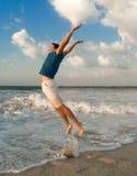счастливый человек скачки около моря Стоковое Фото