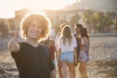 Счастливый человек стоя на пляже при друзья показывая большой палец руки вверх Стоковая Фотография