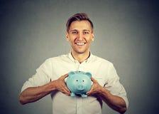 Счастливый человек с голубой копилкой стоковые изображения