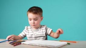 Счастливый чертеж ребенка с карандашами в альбоме, изолированном на сини акции видеоматериалы
