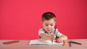 Счастливый чертеж ребенка с карандашами в альбоме, изолированном на пинке видеоматериал
