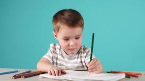 Счастливый чертеж ребенка с карандашами в альбоме, изолированном на сини сток-видео