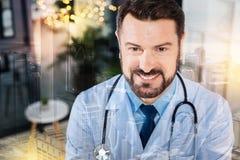 Счастливый эмоциональный доктор усмехаясь пока был на работе стоковое фото