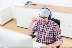 Счастливый gamer на его настольном компьютере стоковое фото