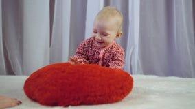 Счастливый newborn младенец усмехаясь и играя с сердцем видеоматериал