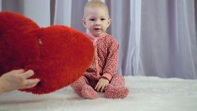 Счастливый newborn младенец усмехаясь и играя с сердцем акции видеоматериалы