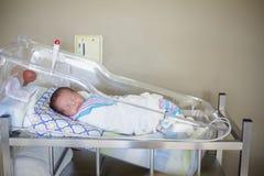 Счастливый newborn ребёнок спать в кровати палаты Стоковая Фотография