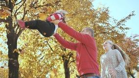 Счастливый outdoors семьи играя с упаденными листьями в солнечной погоде осени Отец бросает вверх его любимую дочь сток-видео