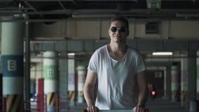 Счастливый smilling человек в солнечных очках и белой футболке идя в подземную парковку движение медленное сток-видео