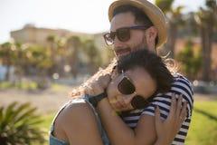 Счастливый snuggle молодой женщины к ее парню снаружи стоковая фотография rf