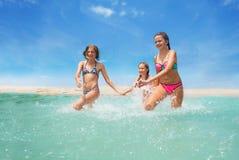 3 счастливых девушки бежать в брызгать моря Стоковая Фотография RF