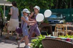 2 счастливых девушки идя на улицу с baloons во время дня предохранения от детей стоковое фото rf