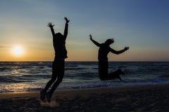 2 счастливых девушки имея потеху и положение с поднятыми оружиями на предпосылке моря захода солнца Стоковое Изображение
