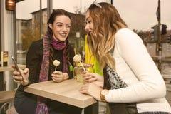 2 счастливых девушки используя smartphone Стоковые Изображения RF