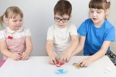 2 счастливых девушки и мальчик играют с обтекателями втулки на таблице Стоковая Фотография