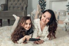 2 счастливых девушки, мать и дочь лежат на поле в комнате украшенной рождеством, используют мобильный телефон для доступа к интер Стоковые Изображения RF