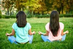 2 счастливых девушки сидят на траве Стоковые Фотографии RF