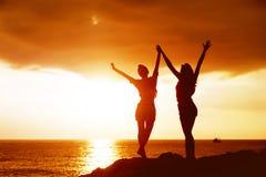 2 счастливых девушки с поднятыми оружиями на предпосылке моря захода солнца Стоковые Изображения
