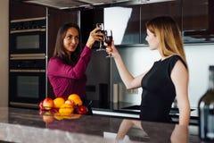 2 счастливых делового партнера поднимая стекла вина предлагая здравицу для успешного взаимного сотрудничества Стоковое Изображение RF