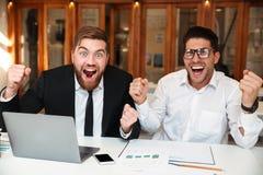 2 счастливых делового партнера при поднятые руки смотря камеру Стоковое Изображение RF