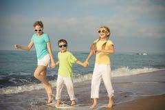 3 счастливых дет бежать на пляже на времени дня Стоковое Изображение