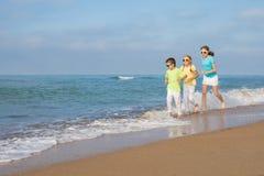 3 счастливых дет бежать на пляже на времени дня Стоковая Фотография