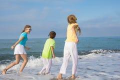 3 счастливых дет бежать на пляже на времени дня Стоковое Изображение RF