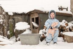 2 счастливых дет в одеждах моды зимы едут сани с свиньей игрушки и медведем на мосте через реку Первый снег, fam Стоковое Фото