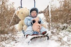 2 счастливых дет в одеждах моды зимы едут сани с свиньей игрушки и медведем на мосте через реку Первый снег, fam Стоковые Фото