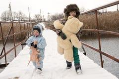2 счастливых дет в одеждах моды зимы едут сани с свиньей игрушки и медведем на мосте через реку Первый снег, fam Стоковая Фотография RF