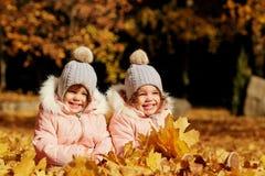 2 счастливых дет в осени одевают в парке Стоковое Фото