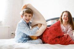 2 счастливых дет в пижамах празднуя партию пижамы Preschool и школьник и девушка имея потеху совместно Стоковая Фотография