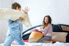 2 счастливых дет в пижамах празднуя партию пижамы Preschool и школьник и девушка имея потеху совместно Стоковые Изображения