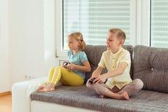 2 счастливых дет играя видеоигры дома Стоковые Фотографии RF