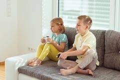 2 счастливых дет играя видеоигры дома Стоковые Изображения