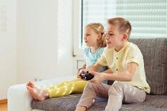 2 счастливых дет играя видеоигры дома Стоковое фото RF