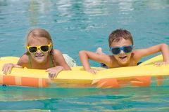 2 счастливых дет играя на бассейне на времени дня Стоковые Изображения RF