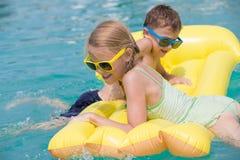 2 счастливых дет играя на бассейне на времени дня Стоковое Фото