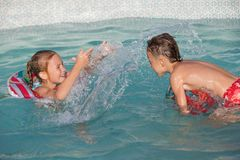 2 счастливых дет играя на бассейне на времени дня Стоковые Изображения