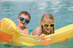 2 счастливых дет играя на бассейне на времени дня Стоковое Изображение