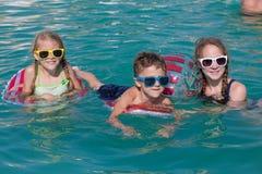 3 счастливых дет играя на бассейне на дне tim Стоковые Фотографии RF