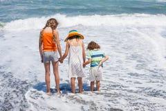 3 счастливых дет играя на пляже на времени дня Стоковая Фотография RF