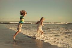 2 счастливых дет играя на пляже на времени дня Стоковая Фотография