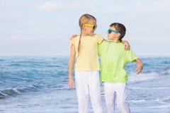 2 счастливых дет играя на пляже на времени дня Стоковая Фотография RF