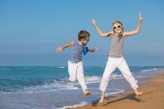 2 счастливых дет играя на пляже на времени дня Стоковые Изображения