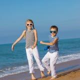 2 счастливых дет играя на пляже на времени дня Стоковое Изображение